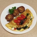A yummy breakfast of Greek omelet (with black olives, spinach, feta and tomato) served alongside salmon cakes
