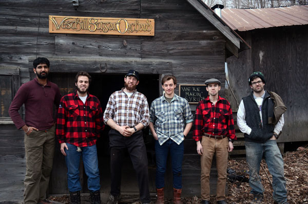 "Six men in plaid shirts stand in front of a sugar shack. A sign behind them reads ""West Hill Sugar Orchard""."